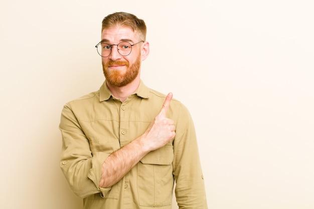 陽気な笑みを浮かべて、幸せな感じと側と上を指している若い赤い頭の男、ベージュの壁の上のコピースペースでオブジェクトを表示