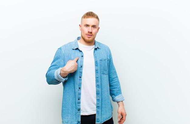 Молодой блондин, одетый в джинсовую рубашку, чувствует себя смущенным, озадаченным и неуверенным, указывая на себя, спрашивая себя и спрашивая, кто, я? над белой стеной
