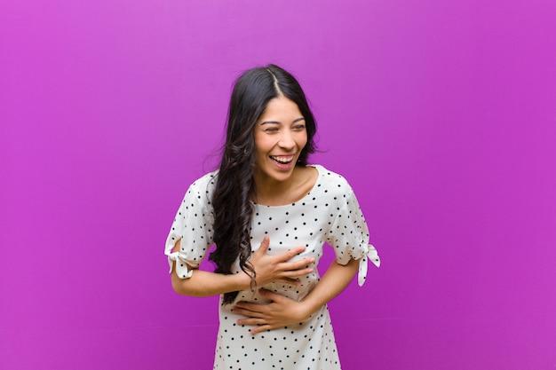 いくつかの陽気な冗談で大声で笑って、幸せで陽気な感じ、紫色の壁を越えて楽しんで若いきれいな女性