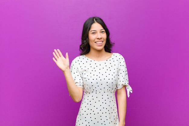若いきれいな女性の笑顔で楽しく、元気よく、手を振って、歓迎と挨拶、または紫色の壁に別れを告げる
