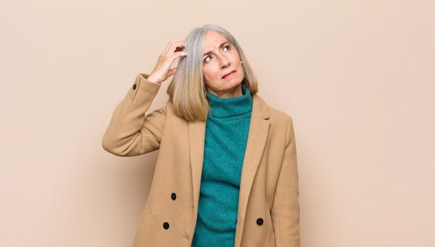 Симпатичная женщина старшего или среднего возраста чувствует себя озадаченной и растерянной, чешет голову и смотрит в сторону