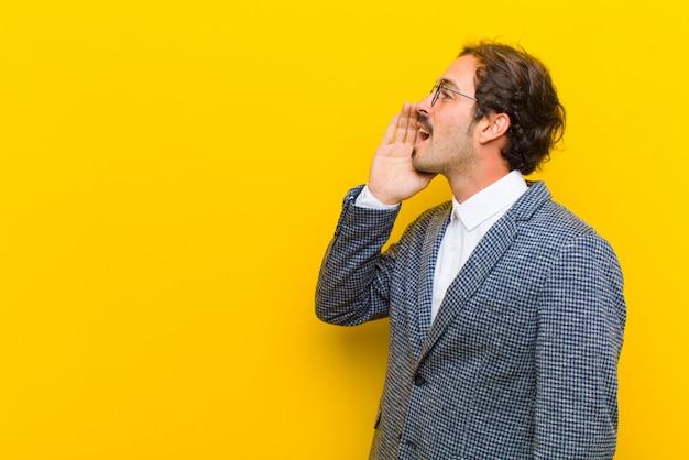 若いハンサムな男のプロフィール、幸せと興奮を探して、叫び、オレンジ色の壁の上の側のスペースをコピーする呼び出し
