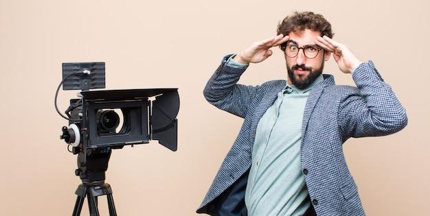 Телеведущий выглядит сосредоточенно, вдумчиво и вдохновенно, мозговой штурм и воображение с руками на лбу