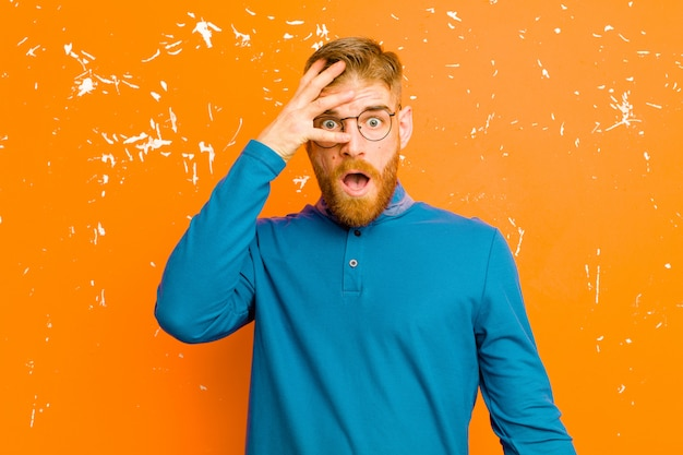 Молодой рыжеволосый мужчина выглядит шокированным, напуганным или испуганным, закрывая лицо рукой и заглядывая между пальцами на оранжевую гранжевую стену