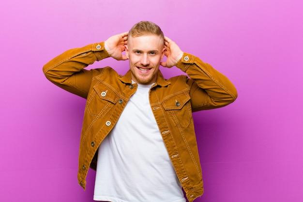 Молодой блондин, выглядящий счастливым, беззаботным, дружелюбным и расслабленным, наслаждающимся жизнью и успехом, с позитивным отношением к фиолетовой стене