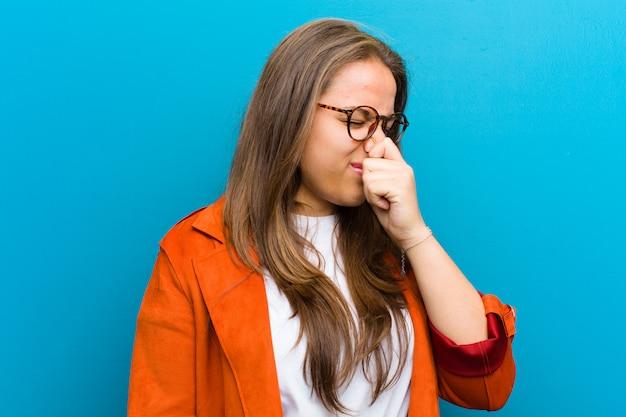 若い女性はうんざりして、青い壁に対して悪臭と不快な悪臭の臭いを避けるために鼻を保持
