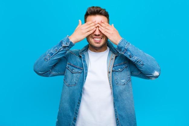 Молодой латиноамериканский человек улыбается и чувствует себя счастливым, закрывая глаза обеими руками и ожидая невероятного сюрприза на фоне голубой стены