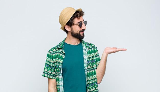 Молодой турист, чувствуя себя счастливым и небрежно улыбаясь, глядя на объект или концепцию держал на руке на стороне против белой стены