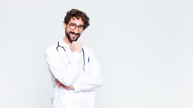 若い医者は笑みを浮かべて、人生を楽しんで、コピースペース壁にあごに手で幸せ、フレンドリー、満足、のんきな感じ