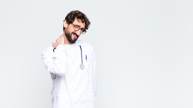 Молодой доктор человек чувствует себя тревожно, плохо, больным и несчастным, страдает от боли в животе или гриппа против копирования пространство стены
