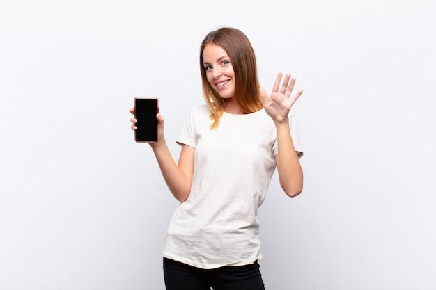 赤い頭のきれいな女性の笑顔で幸せに、元気に、手を振って、歓迎と挨拶、またはスマートフォンを持って別れを告げる