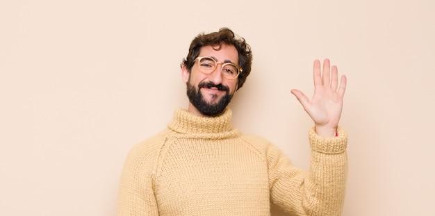 楽しく、元気よく笑って、手を振って、歓迎して挨拶する、または平らな壁に別れを告げるクールな若者