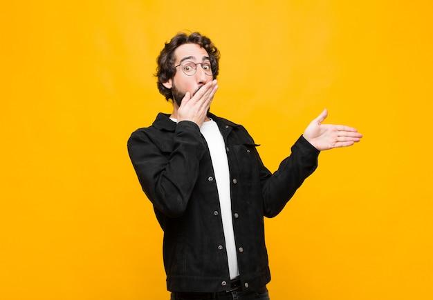 幸せ、ショック、驚きを感じて、手で口を覆っているとオレンジ色の壁に対して横方向のコピースペースを指している若いクレイジーハンサムな男