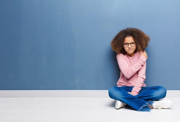 Афро-американская маленькая девочка, чувствующая себя взволнованной, больной, больной и несчастной, страдает от боли в животе или гриппа, сидя на полу