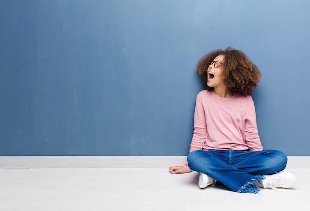 アフリカ系アメリカ人の少女が猛烈に叫んで、積極的に叫んで、ストレスと怒って床に座って見て