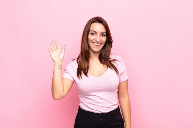幸せで元気な笑顔、手を振って、歓迎と挨拶、またはピンクの壁に別れを告げる若いきれいな女性