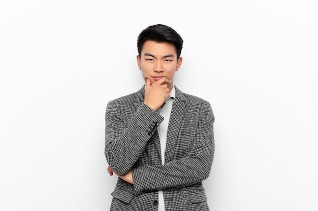Молодой китаец ищет серьезного, растерянного, неуверенного и вдумчивого, сомневающегося среди вариантов или вариантов на фоне плоской цветной стены