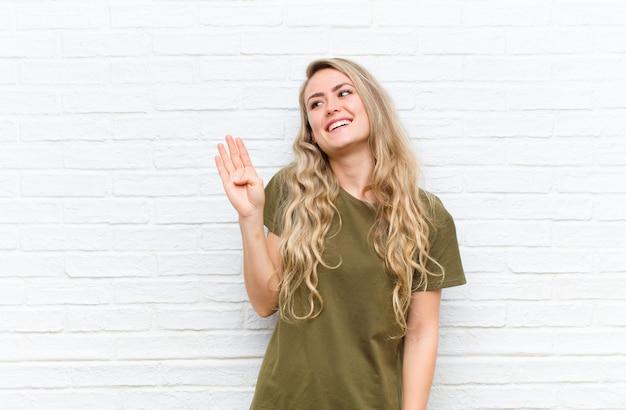 幸せで元気な笑顔、手を振って、歓迎と挨拶、またはレンガの壁に別れを告げる若いブロンドの女性