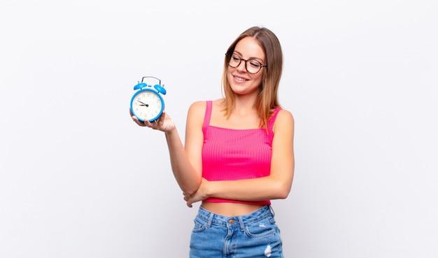 目覚まし時計を押しながら概念を表現する赤い頭のきれいな女性
