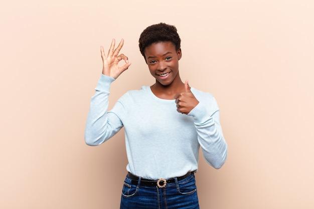 Молодая красивая черная женщина чувствует себя счастливой, изумленной, удовлетворенной и удивленной, показывая хорошо и недурно жестами, улыбаясь
