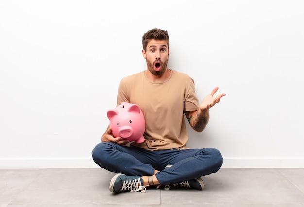 貯金箱を持ってストレスと恐怖の表情で、非常にショックと驚き、不安とパニックを感じます
