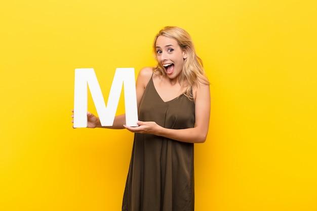 Молодая блондинка удивлена, шокирована, поражена, держа букву м в алфавите, чтобы образовать слово или предложение.