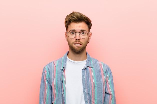 困惑し混乱している若い男が、ピンクの壁に対する問題の答えを知らず、神経質なジェスチャーで唇をかむ