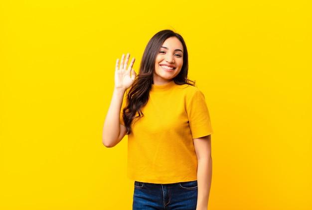 若いラテン系のきれいな女性が幸せそうに笑って、手を振って、歓迎して挨拶するか、フラットな壁に別れを告げる