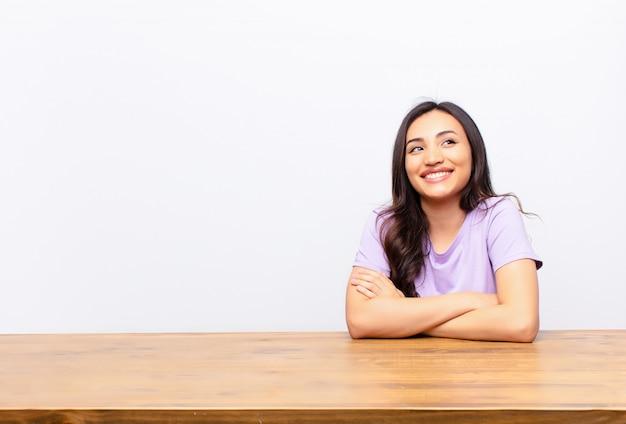 若いラテン系のきれいな女性の幸せ、誇りに思って、希望に満ちた、疑問や考え、平らな壁に組んだ腕でスペースをコピーするために見上げる