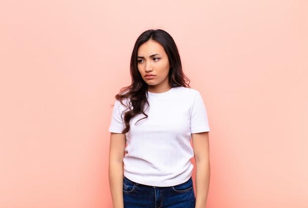 悲しい、動揺または怒りを感じ、否定的な態度で側にいる、平らな壁に対する意見の相違に眉をひそめている若いラテン系のきれいな女性