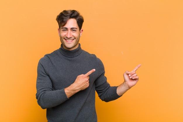 Молодой красавец счастливо улыбаясь и указывая в сторону и вверх обеими руками, показывая объект в копией пространства против оранжевой стены