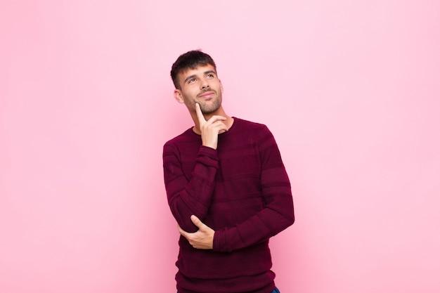 幸せそうに笑って、空想や疑い、ピンクの壁に対して側にいる若いハンサムな男