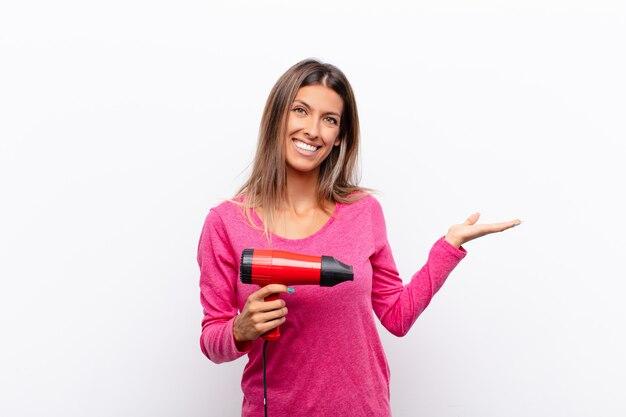 若い可愛い女性が元気に笑顔、幸せな気持ち、ヘアードライヤーで手のひらでコピースペースの概念を示します。