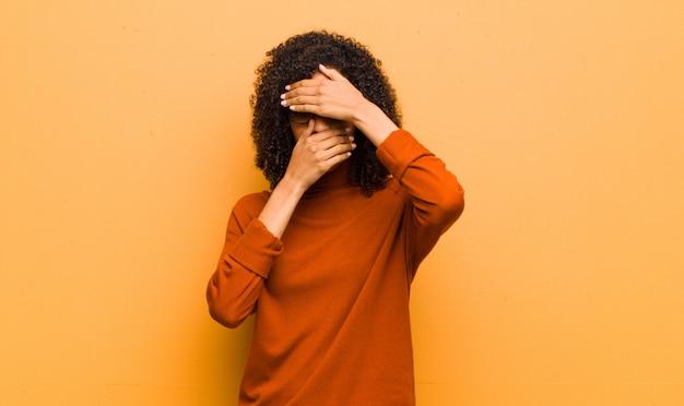 ノーと言って両手で顔を覆っている若いかなり黒人女性!写真を拒否したり、オレンジ色の壁に写真を禁止したりする