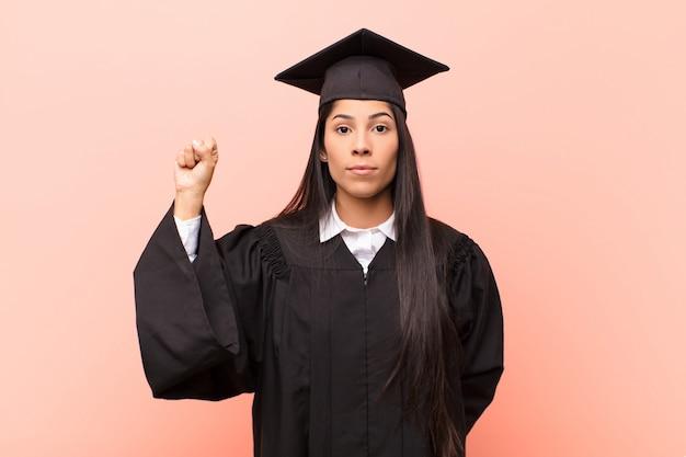 若いラテン女性の学生は深刻で、強く、反抗的で、拳を上げ、抗議し、革命のために戦っている