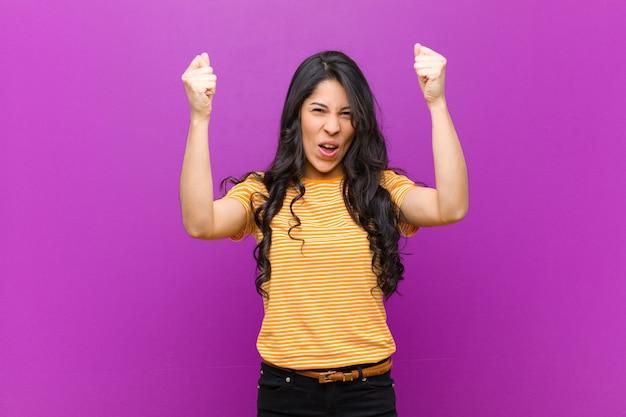 勝者のような信じられないほどの成功を祝っている若いかなりラテン女性、興奮して幸せそうに言ってそれを取ってください!紫色の壁に対して