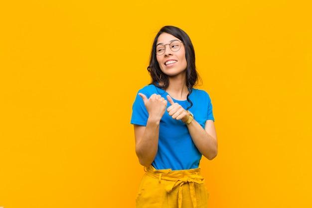 陽気にそしてさりげなく側にコピースペースを指して、オレンジ色の壁に満足して満足している感じ笑顔若いかなりラテン女性