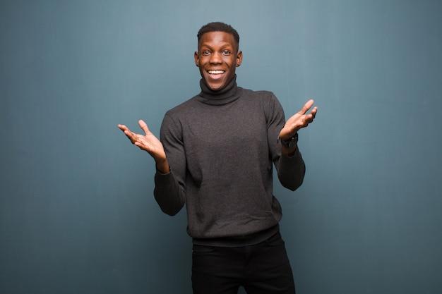 Молодой афроамериканский темнокожий мужчина, выглядящий счастливым и взволнованным, шокирован неожиданным сюрпризом, обе руки открыты рядом с лицом к стене