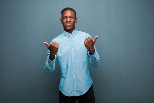 若いアフリカ系アメリカ人の黒人男性が嬉しそうに笑って、幸せそうに見えて、両親指でのんきでポジティブな感じ