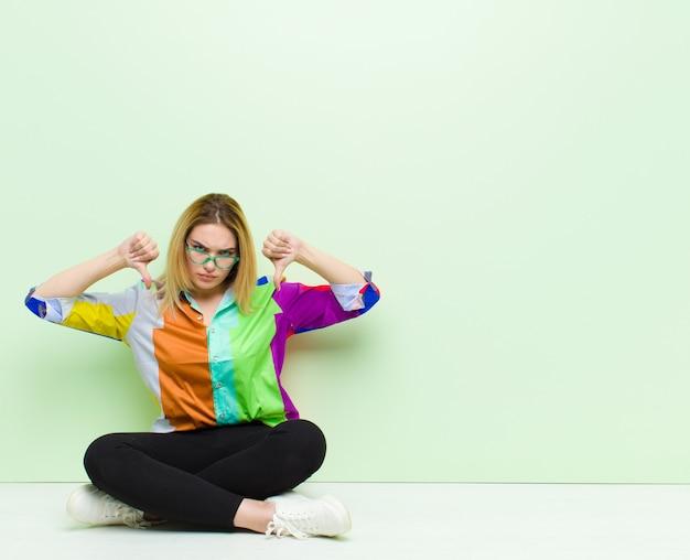悲しい、失望した、または怒っている探している若いブロンドの女性、床に座ってイライラした感じの不一致で親指を表示