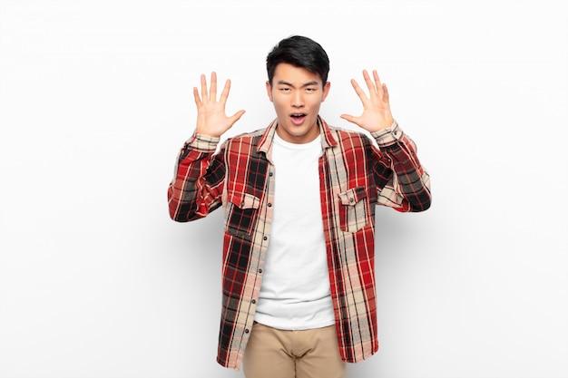 フラットカラーの壁に頭の横にある手でパニックや怒り、ショック、恐怖、激怒で叫んでいる若い中国人男性