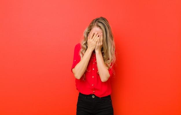 悲しい、欲求不満、緊張、落ち込んで、赤い壁に泣きながら両手で顔を覆っている若いブロンドの女性
