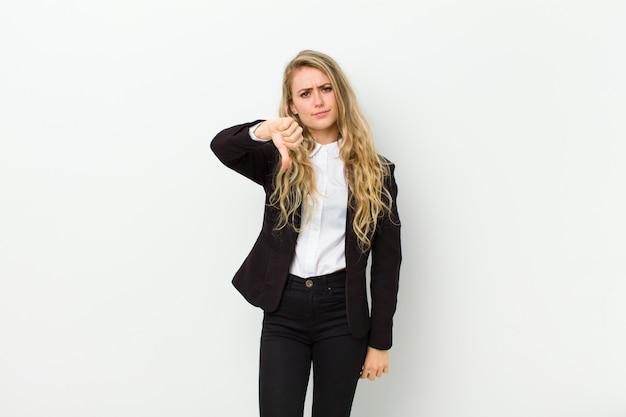 若いブロンドの女性が白い壁に対して深刻な表情で親指を下に見せて、怒り、イライラ、失望、または不満を感じている