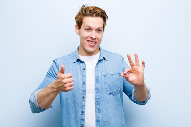 Молодой рыжий мужчина, чувствуя себя счастливым, удивленным, довольным и удивленным, показывая хорошо и недурно жестикулирует, улыбаясь на фоне голубой стены