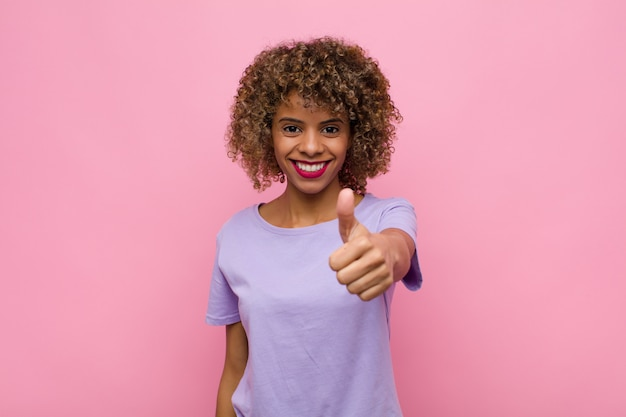 誇りに思って、のんき、自信、幸せを感じて、ピンクの壁に対して親指で積極的に笑顔の若いアフリカ系アメリカ人女性