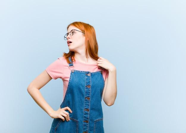 若い赤い頭のきれいな女性のストレス、不安、疲れ、欲求不満の感じ、シャツの首を引っ張って、問題に不満を探して