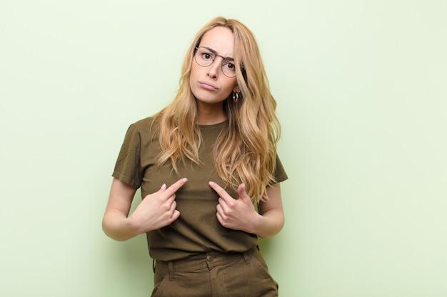混乱し、いぶかしげな表情で自己を指しているかなりブロンドの若い女性、ショックを受け、驚いてフラットカラーの壁に選ばれる
