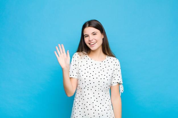 若いきれいな女性が楽しくて元気よく笑って、手を振って、歓迎して挨拶するか、青い壁に別れを告げる