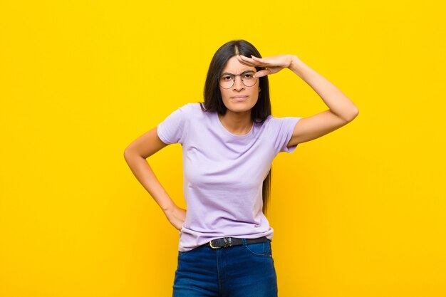 かなり遠くを見て、平らな壁を見て、検索して額に手で戸惑い、驚いた若いかなりラテン女性