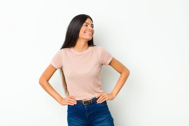 幸せ、陽気、自信を持って探している若いかなりラテン女性、誇らしげに笑って、平らな壁に腰に両手で側を見ている